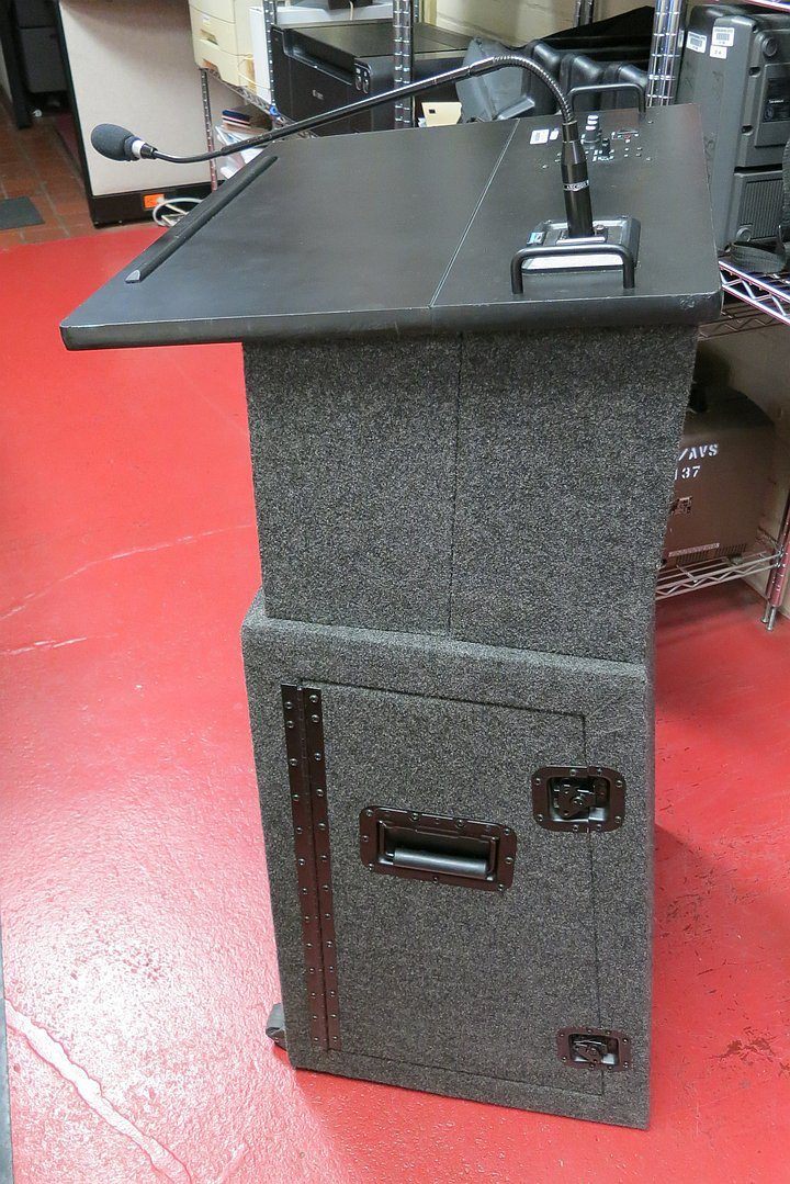 Black and gray lectern with wired microphone and rolling carrying case