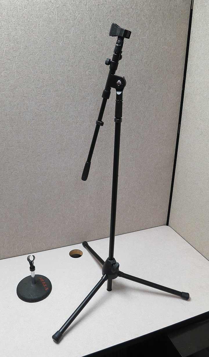 Small tabletop microphone stand alongside a taller, telescoping tripod stand